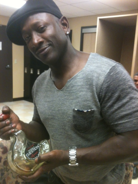 Joe Torry holding a bottle of Cuestión.